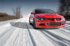 Red sport car driving speed on road at winter daytime Stock Photography