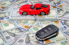 Red sport car with keys on money background. Red sport car with keys on american dollars bills paper money background Royalty Free Stock Photos