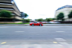 Red sport car moving fast, panning. Red sport car with one person inside. Car is moving fast, panning. Photo taken on overcast day in Glasgow. Buildings and Royalty Free Stock Image