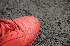 Red sport shoes. A red sport shoes on the black floor royalty free stock photos