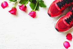 Red sport shoes and red roses on white wooden background, Valen. Tines sports background and greeting card for any anniversary holiday background concept top royalty free stock photo