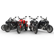 Red sports bike stands out amongst black ones Stock Image