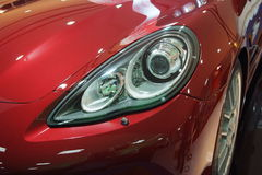 Red sports car. A face of a modern sports car in a city Stock Photos