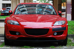 Red Sports Car. A photo taken on the front view of a red sports car at a parking lot Stock Photos
