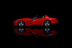 Red sports car. Stylish red sports car reflecting on black background Royalty Free Stock Photography