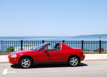 Red Sports Car. A red sports car parked on the street overlooking the water Royalty Free Stock Photography