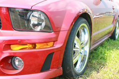 Red sports car. Fragment of the red sports car costing on the ground Royalty Free Stock Photography
