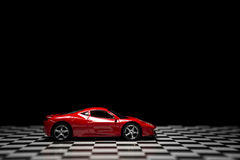 Red Sports car. On a black background and checked floor Stock Photos