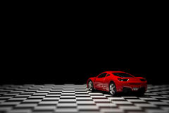 Red Sports car. On a black background and checked floor Royalty Free Stock Photography