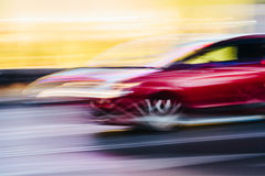 Red Sports Car in a Blurred City Scene Royalty Free Stock Image