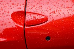 Red Sports Car Door. A closeup shot of a red sports car door with rain spots Royalty Free Stock Photos