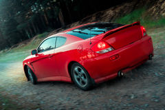 Red sports car moves over rough terrain Stock Photography