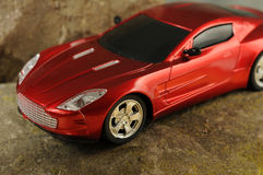 Red sports car. Radio controlled red sports car on gray rock Royalty Free Stock Images
