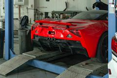 Red sports car raised on a lift in a car repair shop, rear bumper royalty free stock images