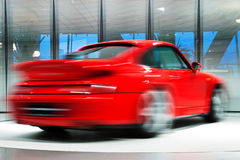 Red Sports Car on Rotating Platform. Red sports car turns on a rotating platform, long exposure Royalty Free Stock Photo