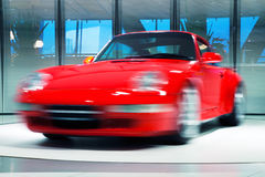 Red Sports Car on Rotating Platform. Red sports car turns on a rotating platform, long exposure, motion blur Royalty Free Stock Images