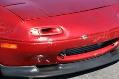 Unusual turn signal light on red sports car with damage to fender. Stock Photography