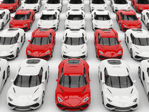 Red sports cars in formation amongst white cars. Red sports cars in formation among white cars Royalty Free Stock Photos