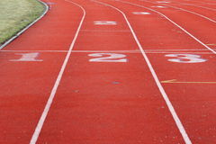 Red sports track. Part of red sports track with white lines and showing numbered starting points Royalty Free Stock Image