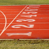 Red sports track with 8 lanes. Section of red eight lane sports track with white lines showing numbered starting points royalty free stock photography