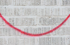 Red spray paint on white brick wall Royalty Free Stock Image