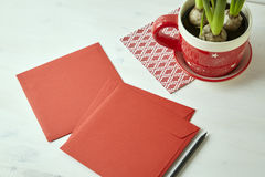 Red square envelopes and pencil on white wooden table. Blank space for stationery design layout Royalty Free Stock Images