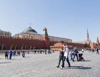 Red Square. Moscow - April 12, 2015: Citizens and tourists walking on Moscow's Red Square and Lenin's mausoleum and see the Russian flag over the building of the royalty free stock photos
