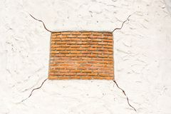 Red square shape brick on white background with cracks. Taken outdoor Royalty Free Stock Image