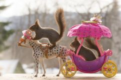 Red squirrels sit on a royal horse and chariot. Red squirrels sit on an royal horse and chariot Royalty Free Stock Photography