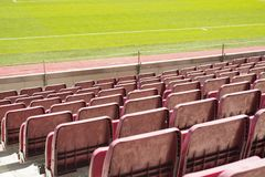 Red stadium seat in soccer stadium. Green grass on background Stock Images