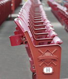 Red Stadium Seats. A red stadium seat in detail with rows of seats blurred behind the main seat at a baseball stadium royalty free stock photos