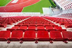 Red stadium seats with red running track and green grass. Royalty Free Stock Photos