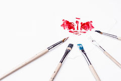 Red stain and paint brushes on a white background Stock Photos