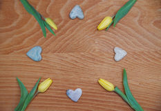 Red stained wooden background with tulips and soapstone hearts Stock Photo