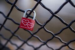 Red and Stainless Steel 2 Hearts Padlock on Black Cyclone Fence during Daytime Royalty Free Stock Image