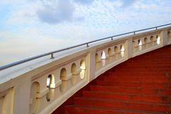 The red stairs with the white railing on the background of the blue sky. Stock Images