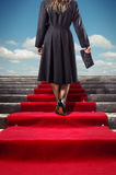 Red Stairway. Elegant woman in black coat climbing a red carpet stairway Stock Images
