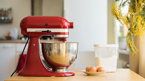 Red stand mixer with ingridients. Red stand mixer with eggs and flour Royalty Free Stock Images