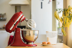 Red stand mixer mixing cream. With eggs, flour, flowers Stock Photos
