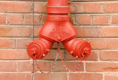 Red Standpipe Against Brick Stock Photography
