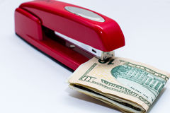 Red staple and a stack of dollar bills in it Stock Photos