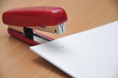 Red stapler fastens white paper Stock Photography