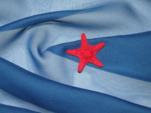 Red star and blue fabric. Red star on blue fabric suitable as background Stock Photography