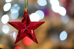 Red star with bokeh Xmas tree lights Royalty Free Stock Images