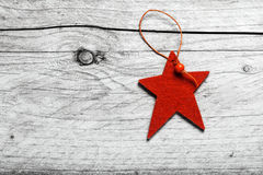 Red star Christmas decoration on grungy wood. Red star Christmas decoration on grungy weathered textured wood with copyspace for your seasonal greeting royalty free stock photo