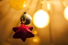 Red star on a gold background. Glowing fuzzy balls. Christmas decorations Stock Photos