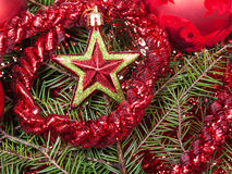 Red star, tinsel on Christmas tree background Stock Image