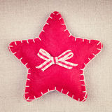 Red star with wooden button and bow on vintage fabric Stock Photos