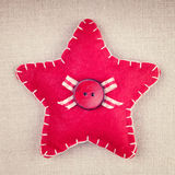 Red star with wooden button and bow on vintage fabric surface Stock Photos