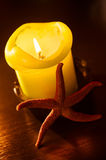 Red Starfish leaning by the candle Stock Photos